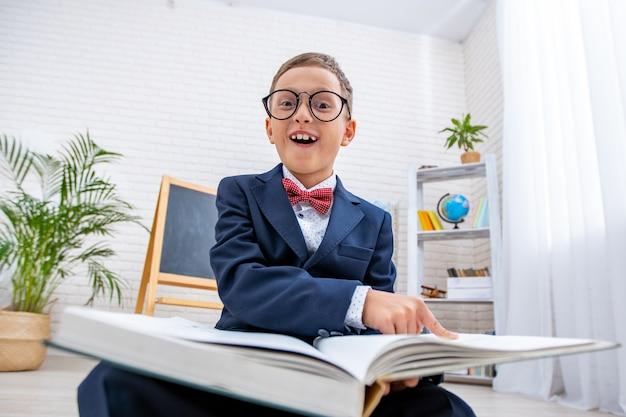 Nerd da escola com óculos aponta para livro e ri.