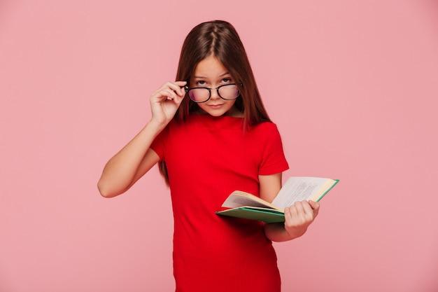 Nerd de menina séria no vestido, olhando através dos óculos durante a leitura