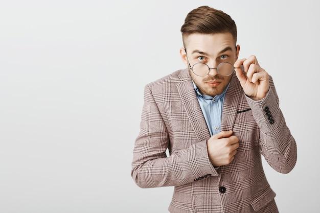 Nerd inseguro de óculos e terno parecendo tímido e desconfiado
