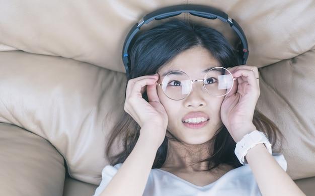 Nerd menina asiática com óculos está ouvindo música em seu fone de ouvido