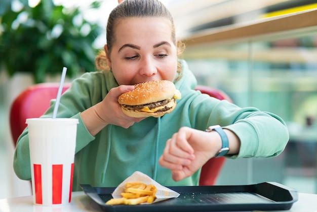 Nervosa, estressada, garota com fome, mulher com pressa, mordendo com pressa, comendo hambúrguer grande, batatas fritas e refrigerante olhando para relógios, verificando as horas. amo junk food rápido. estilo de vida não saudável. engordando, comendo demais