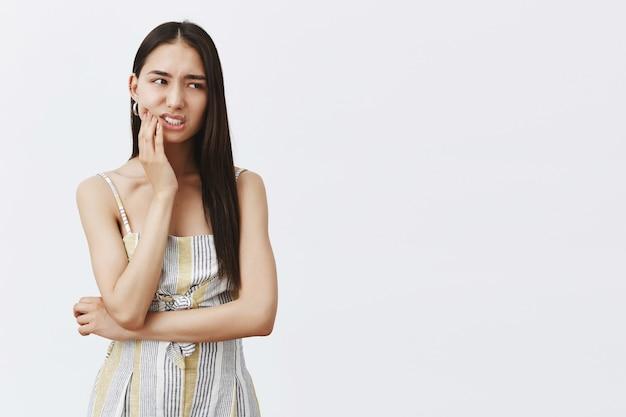 Nervosa, preocupada, atraente e elegante modelo feminina em traje combinando, segurando a palma da mão no queixo e olhando para a direita ansiosamente