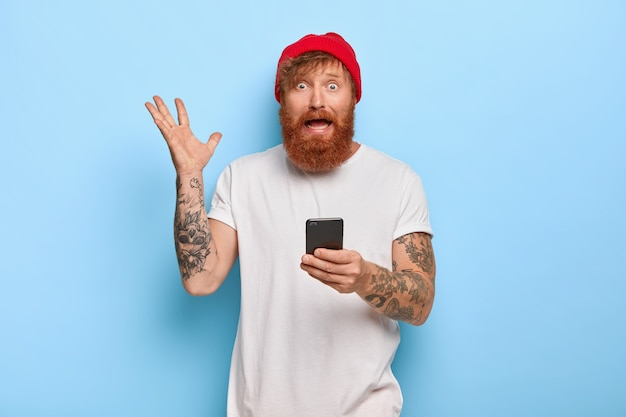Nervoso e preocupado, o ruivo barbudo levanta a mão, segura o celular, usa chapéu vermelho e camiseta branca, usa tecnologia moderna, sente-se perplexo e preocupado, verifica a lista de contas online, gesticula com raiva Foto gratuita