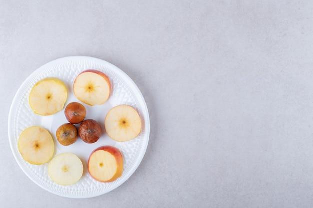Nêspera e maçãs fatiadas no prato, no mármore.
