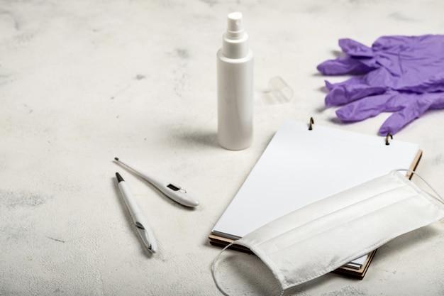 Nessary coisas anti-vírus na vida diária para a higiene e para impedir a propagação do vírus. desinfetante para as mãos, máscara cirúrgica, termômetro digital e caderno sobre fundo branco.