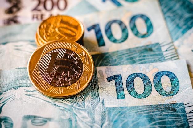 Nesta foto a ilustração sendo exibidas notas de cento e duzentos reais e uma moeda de um real em destaque. o real é o dinheiro atual no brasil.