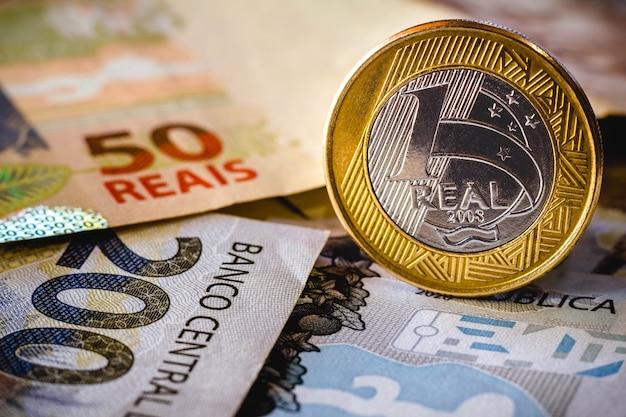 Nesta foto ilustração sendo mostradas notas de cinquenta e duzentos reais e uma moeda de um real em destaque o real é o dinheiro atual no brasil