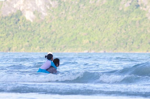 Neta abraça ou abraça a avó no mar.