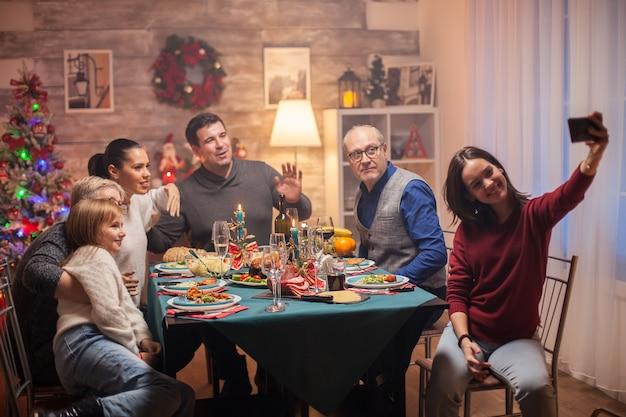 Neta alegre tomando uma selfie com a família na celebração do natal.