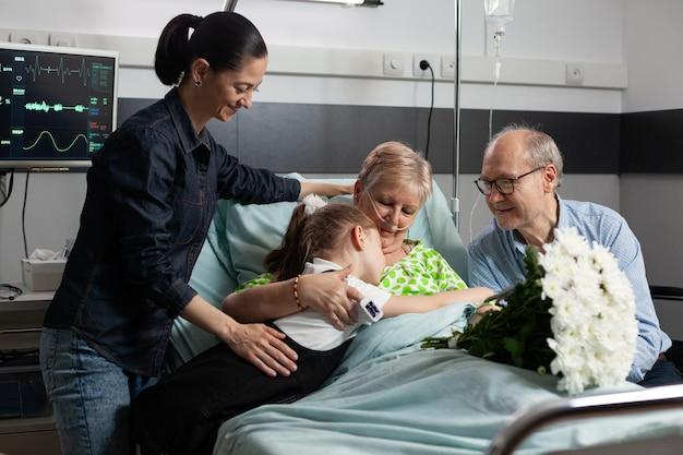 Neta carinhosa abraçando a avó doente enquanto a visitava na enfermaria do hospital