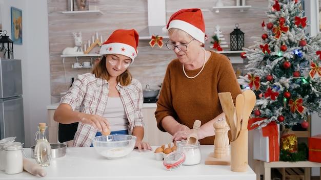 Neta com a neta quebrando ovo na tigela da cozinha com ingrediente de farinha