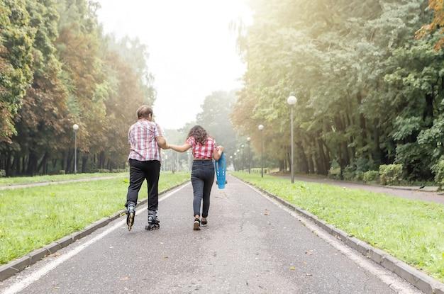 Neta e avó andando de patins e skate no parque