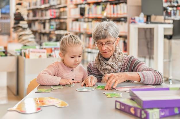 Neta e avó montaram um quebra-cabeça na biblioteca da cidade