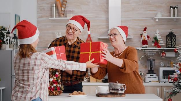 Neta feliz surpreendendo os avós com presente de embrulho com fita.