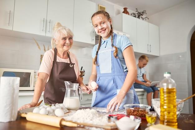 Neta sorridente passando um tempo na cozinha com uma senhora idosa