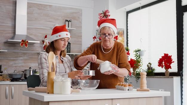 Neta usando a peneira de cozinha enquanto a avó colocando o ingrediente de farinha