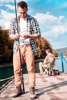 Neto adulto pescando com o avô no cais