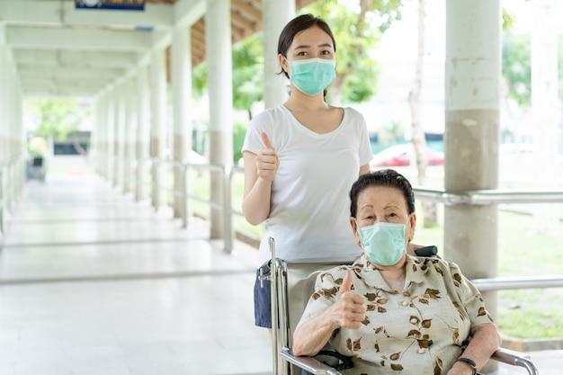Neto asiático novo que cuida de sua avó que senta-se na cadeira de rodas.