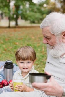Neto com vovô no parque, bebendo chá