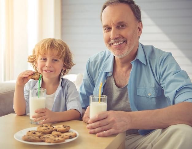 Neto e avô bonito estão bebendo leite