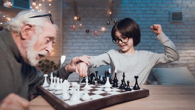 Neto e avô jogando xadrez juntos