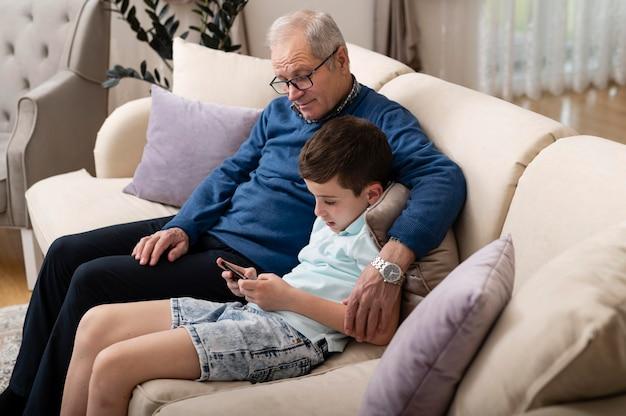 Neto e avô relaxando no sofá