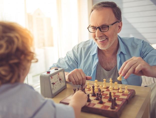 Neto e vovô bonito estão jogando xadrez