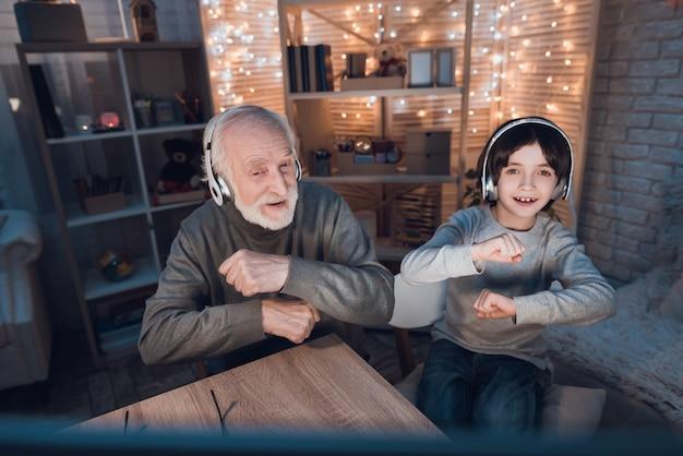 Neto e vovô ouvindo fones de ouvido de música