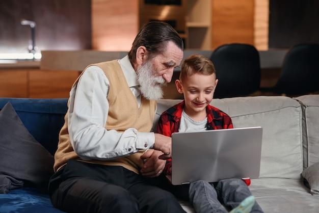Neto está ensinando seu avô a usar o laptop.