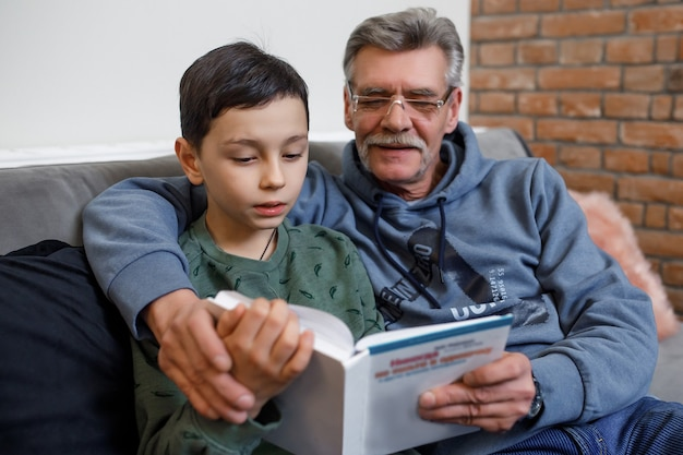 Neto lendo livro com seu avô feliz enquanto está sentado no sofá.