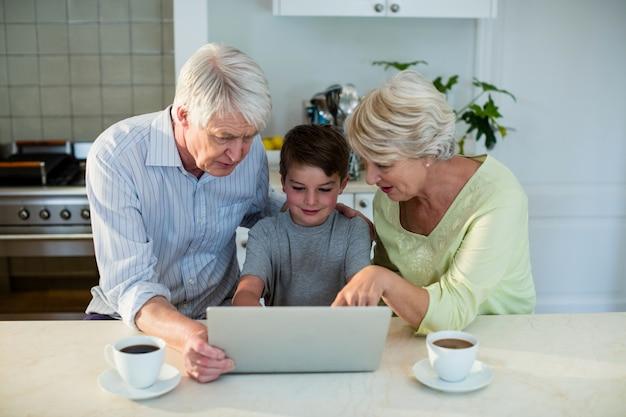 Neto usando laptop com avós