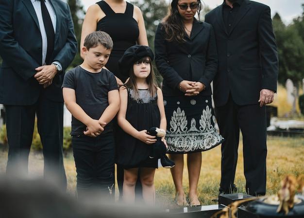 Netos tristes em pé junto ao túmulo