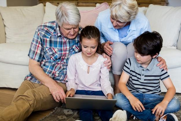 Netos usando laptop com seus avós