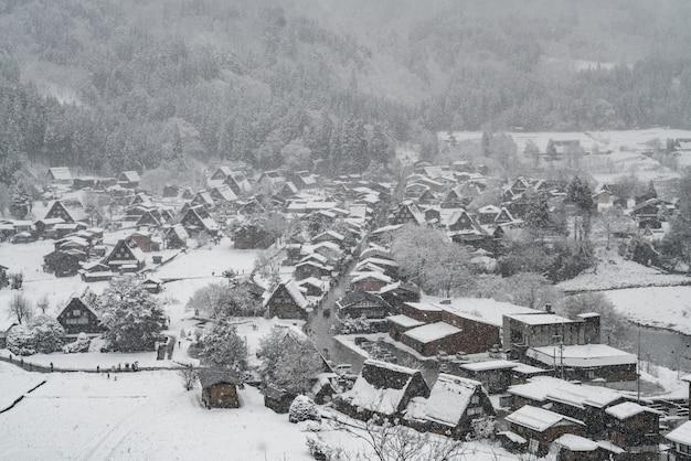 Nevando em uma vila no vale e a neve cobre toda a vila de shirakawago, no japão.