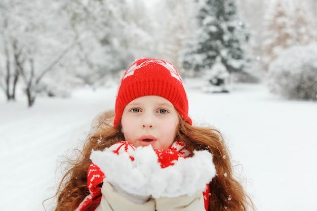 Neve de sopro da menina no parque do inverno.