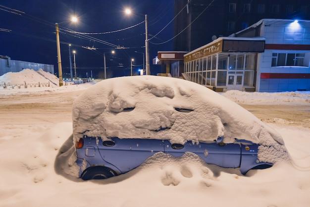 Neve em carros após a queda de neve. cena urbana de inverno.