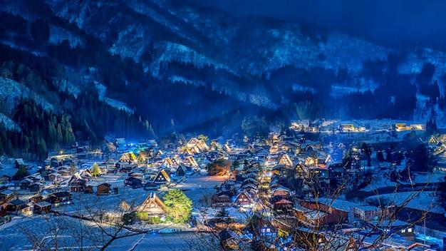 Neve que cai na luz acima do shirakawago no inverno, japão do festival.
