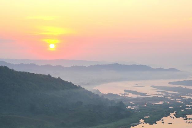 Névoa das montanhas e opinião do nascer do sol de phu huay isan em nong khai, tailândia.