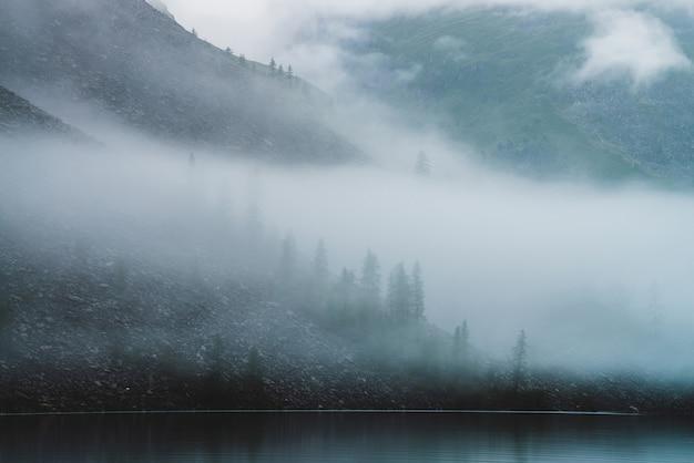 Névoa densa sobre lago tranquilo na montanha