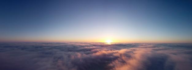 Névoa espessa e céu claro, o sol alaranjado da manhã ilumina as nuvens. foto panorâmica de nevoeiro matinal de outono