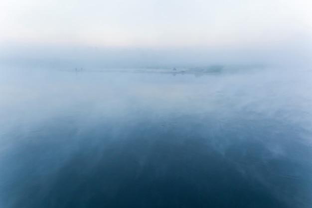 Névoa no rio. névoa matinal no rio com a costa no horizonte, fundo azul desfocado.