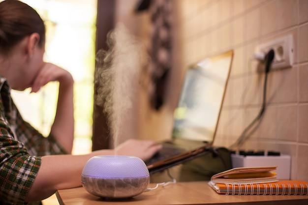 Névoa saindo do difusor de óleo essencial com led roxo enquanto mulher trabalhava no laptop.