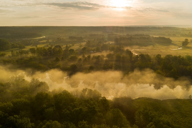 Névoa sobre o rio nos primeiros raios do sol do amanhecer entre a floresta no parque natural. os primeiros raios do sol do amanhecer iluminam a névoa clara sobre o rio.