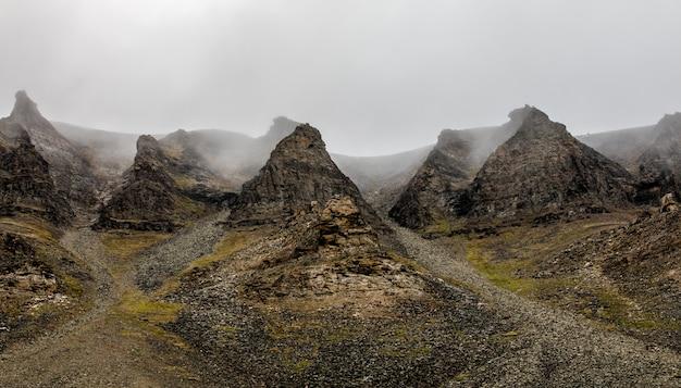 Nevoeiro e falésias, paisagem de pico de montanha. spitsbergen, svalbard, noruega