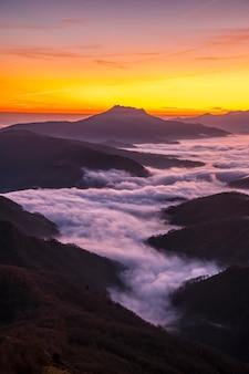 Nevoeiro entre as montanhas do país basco, próximo ao monte larrun, na hora dourada do amanhecer. foto vertical