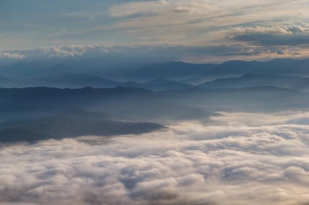 Nevoeiro na montanha com o sol nascendo de manhã