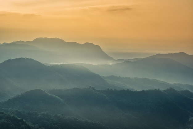 Nevoeiro nas montanhas com céu dramático ao nascer do sol