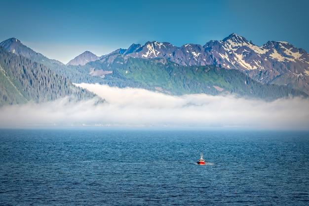 Nevoeiro subindo pelas montanhas no alasca, visto do mar aberto