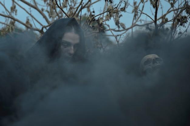 Nevoeiro witchy preto cobrindo o rosto e o crânio de mago
