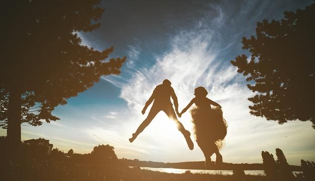 Newlyweds saltar para o pôr do sol